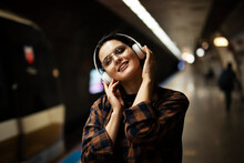 Young Smiling Woman Outdoors. A Young Woman Listening To Music While Waiting For The Train.