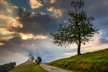 Jamnik, Slovenia - Magical Foggy Summer Morning At Jamnik St.Primoz Church With Small Gravel Road And Tree. The Fog Goes Around The Small Chapel With Blue Sky And Rising Sun At Background