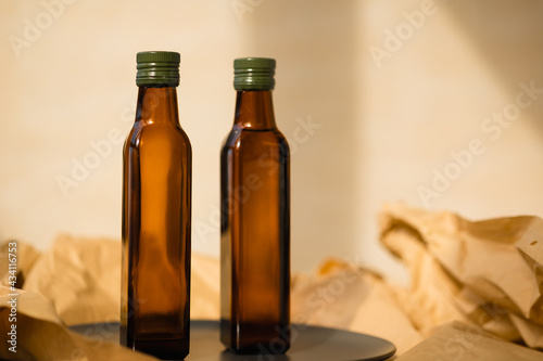 Wallpaper Mural Two glass brown transparent faceted bottles without labels empty and full with vegetable oil with green metal caps stands on a black plate on paper