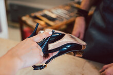 Customer Bringing Shoes To The Shoemaker For A Repair