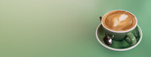 A Hot Vanilla Latte In A Green Ceramic Cup On A Tone On Tone Green Long Background