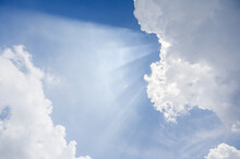 Blue Sky With Sun Rays Penetrates The White Clouds On A Bright Day.