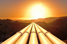 Gas Or Oil Pipeline Pipes In Mountainous Terrain Against The Backdrop Of Sunset. Oil And Gas Or Pipe Industry Concept