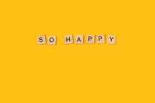 So Happy Palabra Escrita En Cubo De Madera Sobre Un Fondo Amarillo Liso Y Aislado. Vista Superior. Copy Space