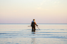 A Man With A Metal Detector And Scoop Searches For Treasures In The Sea.