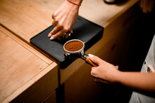 View Of Baristas Hand Tamping Coffee In Portafilter Before Making Fresh Drink