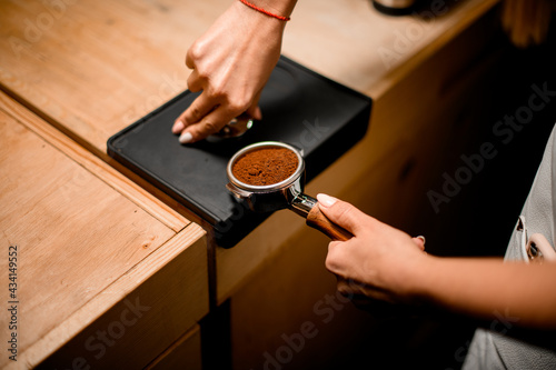 Fotografia view of baristas hand tamping coffee in portafilter before making fresh drink