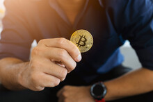 Golden Bitcoin In A Businessman Hand In The Office With Soft Focus And Backlighting. Cryptocurrency Concept