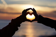 Heart Shape With Hands Of Loving Couple On Sunset Sky Background