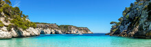 Panoramic View From An Empty Cala Macarelleta, With Turquoise Waters And Blue Sky, In Menorca, Balearic Islands, Spain