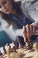 Woman Playing Chess And Moving A Piece