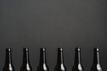 Row Of Identical Dark Bottles Of Alcoholic Drinks With Shiny Surface On Gray Background