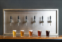 Different Types Of Beer With Foam In Glass Jugs Against Row Of Taps In Bar On Gray Background