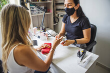 Side View Of Unrecognizable Female Customer Paying To Ethnic Master After Manicure In Nail Salon