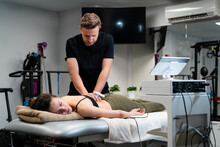 Male Physiotherapist Applying Laser To Back Skin Of Female During Medical Treatment In Hospital