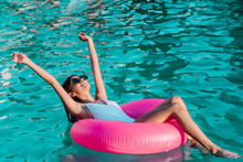 Young Cheerful Female Traveler In Swimwear And Sunglasses Lying With Raised Arms In Inflatable Ring In Swimming Pool