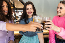 Joyful Young Multiethnic Female Best Friends In Stylish Colorful Outfits Smiling And Clinking Glasses Of Refreshing Juice And Coke In Modern Bar