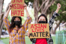 Ethnic Females In Masks And With Stop Asian Hate And Asian Lives Matter Posters Protesting Against Racism In City Street And Looking At Camera