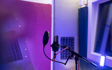 Pop Filter And Modern Dynamic Mic With Wires In Empty Sound Studio On Blurred Background