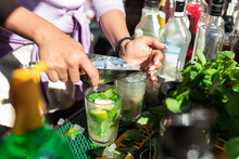 Crop Anonymous Female Barkeeper Adding Ice Cubes Into Glass While Preparing Cold Refreshing Mojito Cocktails In Sunny Outdoor Bar