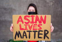 Ethnic Female In Mask And With Carton Placard With Inscription Asian Lives Matter Protesting In City Street And Looking At Camera