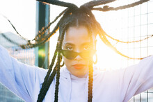Young African American Female With Red Lips And Afro Braids In Sunglasses Looking At Camera In Sunlight Outdoors