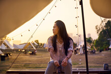 Beautiful Ethnic Asian Female Sitting At Table While Having A Relaxing Time In Camping Area During Holidays During Sunset Looking Away
