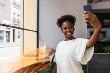 Happy Young African American Female In White Blouse Taking Selfie On Mobile Phone While Sitting At High Table Near Glass Wall In Modern Cafe