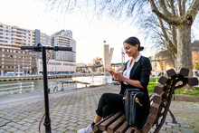 Smiling Ethnic Female Entrepreneur Sitting On Wooden Bench With Crossed Legs Speaking On Cellphone While Looking Away On City Bench Against Scooter