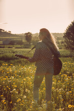 Back View Of Unrecognizable Young Hipster Woman Standing On A Meadow In The Countryside Playing Guitar During Summer Sunlight