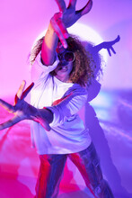 Confident Young African American Female Dancer In Informal Wear And Sunglasses Dancing And Outstretching Arms Towards Camera In Neon Lights In Studio