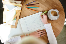 From Above Of Crop Unrecognizable Female Astrologist Taking Notes On Paper With Geometric Drawing At Desk With Cup Of Coffee