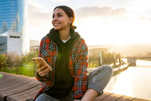Young Smiling Ethnic Female In Casual Wear Text Messaging On Cellphone On Bridge Over River Under Cloudy Sky In Sunlight Looking Away