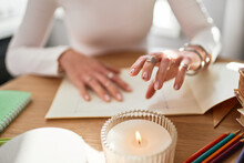 Crop Unrecognizable Astrologist Diving Future At Desk With Paper Album And Flaming Candle In House