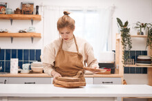 Young Focused Female In Apron With Assorted Wooden Chopping Boards And Plate At Table In Light House