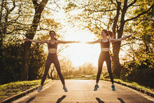 Cheerful Athletic Female Runners Standing On Pathway In Park And Warming Up Arms During Training At Sunset
