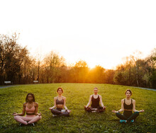 Company Of Diverse Serene Females Sitting In Lotus Pose In Park And Meditating Together With Closed Eyes While Doing Yoga At Sunset In Summer