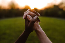 Crop Anonymous Multiethnic Females Holding Hands On Background Of Bright Sun In Sunset Sky While Showing Concept Of Unity And Tolerance
