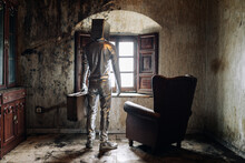Back View Unrecognizable Person Wearing Protective Silver Suit With Box On Head Standing Near Armchair In Shabby Room In Abandoned House