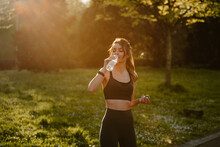 Young Sportswoman Drinking Water During Break From Training In Back Lit