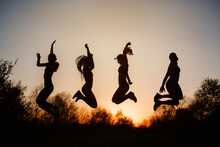 Silhouettes Of Females Jumping Above Ground Against Sky At Sundown In Park