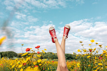 Crop Unrecognizable Female In Bright Footwear Lying With Crossed Legs Among Blossoming Daisies Under Cloudy Blue Sky In Countryside