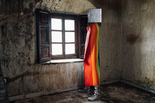 Full Body Unrecognizable Strange Person Wearing Silver Box On Head And Rainbow Flag On Shoulders Standing Near Window In Abandoned Shabby Room
