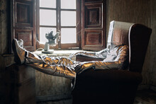 Side View Unrecognizable Person Wearing Protective Silver Suit With Box On Head Resting On Armchair In Shabby Room In Abandoned House