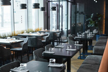 Modern Interior Of Restaurant In Gray Color Furnished Soft Chairs And Black Tables With Glasses And Napkins