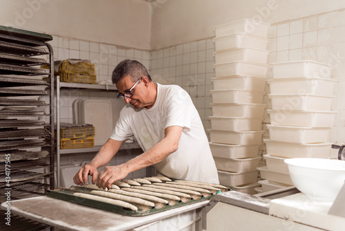 Fotografiet old authentic baker in bakery making organic bread and taking care of it with passion and care