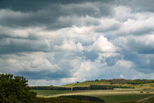 Sunshine Bursts Through Heavy Blue And Grey Rain Cloud On To A Landscape With Open Grassland Meadow, Woodland Copse And A Distant Tree Lined Hill