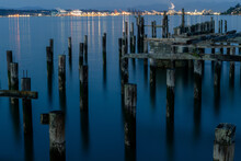 Old Pier Pilings In Calm Water At Night With City In Background