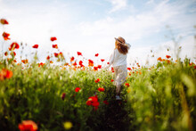 Girl In A Hat With Long Curly Hair Posing In A Field With Red Flowers. Summer Landscape. Warm Colors. Woman Walking Through A Poppy Field. Young Girl In The Spring Flower Garden.