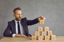 Clever Talented Professional Business Manager Finds Right Effective Rational Solution. Serious Man At Office Desk Puts Final Wooden Cube On Top Of Pyramid With Many Multiple Idea Light Bulb Symbols